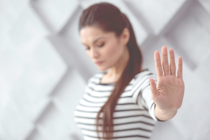 Woman putting her hand up to stop