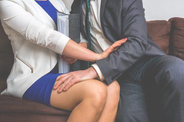 Man putting his hand on woman's leg